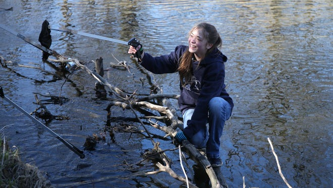 Mahayla Claiser, 13, of Urbandale, uses cat-like balance as she steps out onto a tree limb in the water to grab a piece trash along Walnut Creek in Des Moines on Saturday, April 4, 2015.