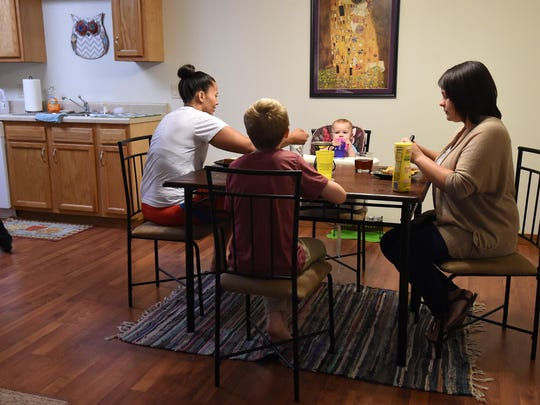 Nikki Mitchell, left, and partner Sarah Reynolds, along with Reynolds' niece and the couple's son, eat lunch at their Mountain Home apartment. The couple spend most of their down time at home.