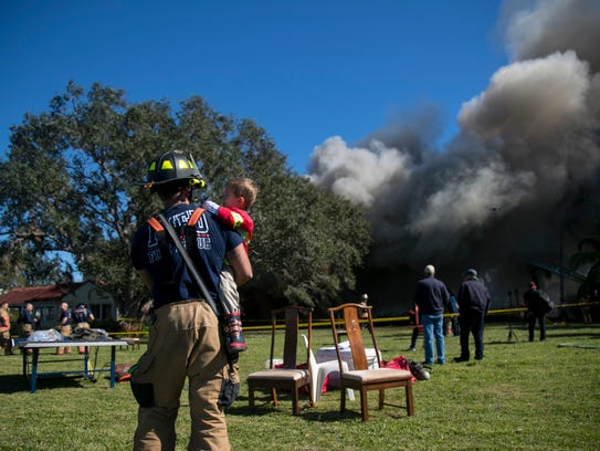 Zach Keegan of the Iona-McGregor Fire Department holds his three-year-old son Tristan on Sunday after a training fire in Fort Myers. The fire department was given the house to burn for training. The property owners are planning to build a bigger home on the riverfront property.