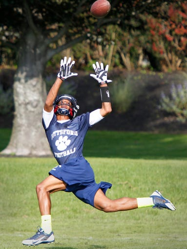 Pittsford receiver Zuril Hendricks goes all out to pull in a long throw down the sidelines during the team's practice at Pittsford Mendon High School.