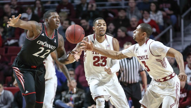 Temple's Jesse Morgan (3) grabs a loose ball in front of teammate Devontae Watson and Cincinnati's Coreontae DeBerry during the first half of an NCAA college basketball game Tuesday, Feb. 10, 2015, in Philadelphia. (AP Photo/)