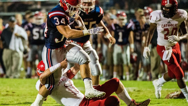 Notre Dame running back Lance Bertrand (34) attempts to break a tackle by Catholic NI linebacker Will Mullen (11) during the Pioneers' win Thursday at Gardiner Memorial Stadium.
