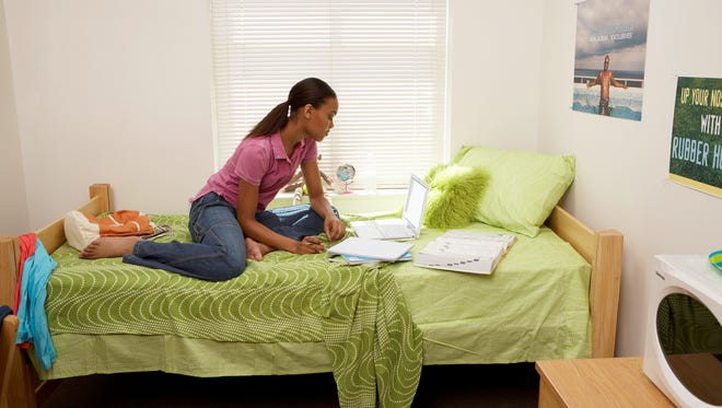 Young woman sitting in dorm room