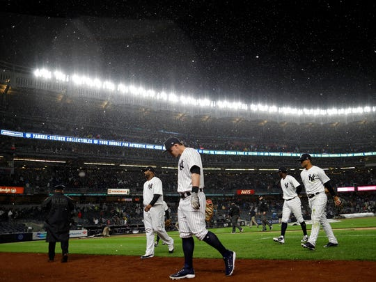 New York Yankees first baseman Tyler Austin (26) heads to the dugout with teammates during a rain delay against the Boston Red Sox during the fifth inning at Yankee Stadium.