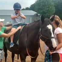 Jacob Borkin rides Painters with the assistance of Patti Gottsacker and Kelsey Lyneis. Painters is a 25-year-old Paint mare that has been part of the Helping Hands Healing Hooves program since its inception.