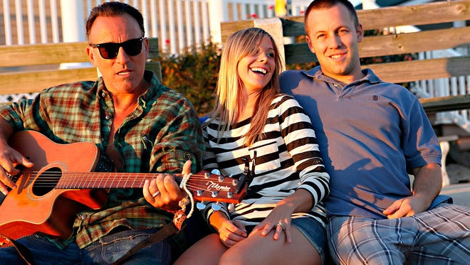 Bruce Springsteen (far left) was hanging out on at the Point Pleasant Beach inlet when Jennifer Smith and Ed Dwyer, both of Brick, happened upon the musician during their engagement photo shoot in 2010.