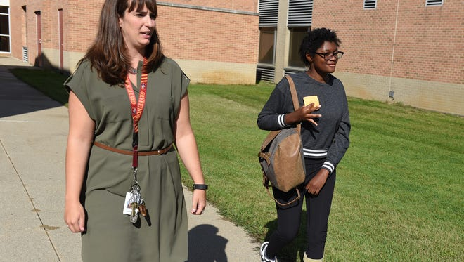 Felicia Simons, right, walks to her school bus after a half day on Sept. 5. with her in-school assistant Caroline Eby. Eby helps Simons navigate the her busy half days at school as she continues to recover from a stroke.