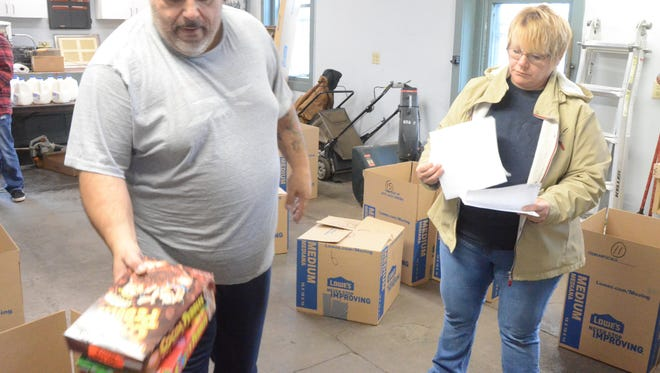 Alphonse Bifulco and Tina Fleming fill boxes with food on Sunday for Thanksgiving meals.