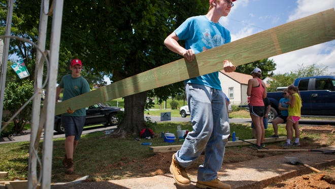 Will Elgin, right, of Columbus, Ohio, carries a board with his brother, Peter Elgin, 15, as they work on repairing a blind Staunton resident's damaged walkway during a week-long volunteer trip with their church on Tuesday, June 16, 2015. The hot temperatures made some of the volunteers sluggish, but they continued working through the day.