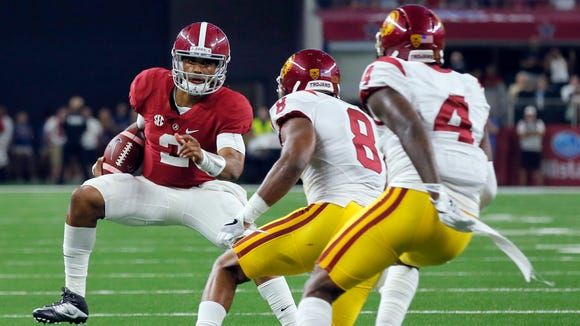 Alabama quarterback Jalen Hurts, left, carries as Southern California defensive back Iman Marshall (8) and defensive back Chris Hawkins (4) defend during the first half of an NCAA college football game Saturday, Sept. 3, 2016, in Arlington, Texas. (AP Photo/Tony Gutierrez)