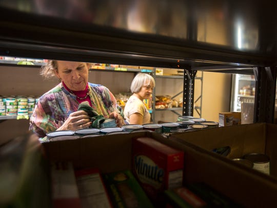 St. Vincent Paul Outreach Food Pantry employees stocks the shelves on Thursday, November 3, 2016 at the St. Vincent Paul Outreach Food Pantry in Marshfield, Wisconsin. 