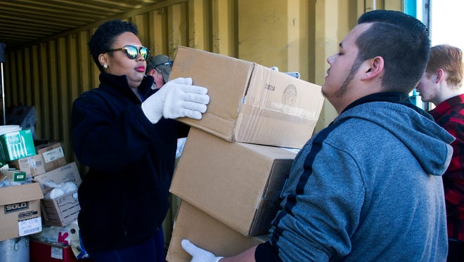 Janae Graves, left, and Diego Vasquez, both with the New America School, help to sort and organize a storage container at El Caldito soup kitchen Monday morning as part of a service project on Martin Luther King Jr. Day.