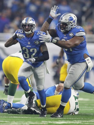Lions safety Tavon Wilson, left, and defensive lineman A'Shawn Robinson celebrate after sacking Packers quarterback Aaron Rogers on Jan. 1, 2017 at Ford Field.