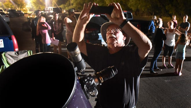 Keith Little uses an app on his mobile phone to help align his reflector telescope during a stargazing gathering of the San Antonio Astronomical Association at McAlister Park  on Oct. 7, 2015 in San Antonio, Texas.  For years, SAAA has set up towering Dobsonians, compact Schmidt-Cassegrains and other powerful telescopes in a McAllister parking lot near some too-well-lit soccer fields. And despite growing light pollution, the group continues to open many a squinted eye to the wonders of the cosmos.  (Billy Calzada/The San Antonio Express-News via AP) RUMBO DE SAN ANTONIO OUT; NO SALES; MANDATORY CREDIT