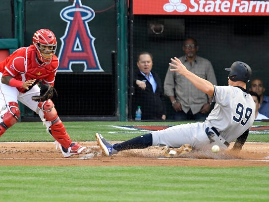 The Yankees' Aaron Judge, right, scores ahead of the tag by Los Angeles Angels catcher Martin Maldonado on an error by  Zack Cozart during the first inning Saturday, April 28, 2018, in Anaheim, Calif.