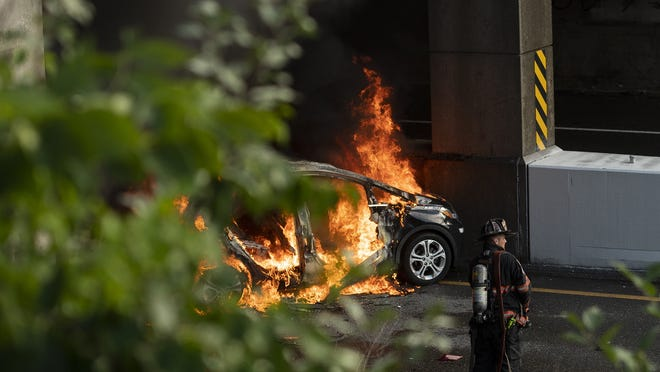 A car is in flames on Route 2 under the Route 13 overpass in Leominster shortly before 6 p.m. Wednesday after a seven-car crash on the highway. The driver escaped with minor injuries.