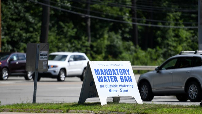 A mandatory water ban sign is placed at the entrance to the Center at Hobbs Brook shopping area on Route 20 in Sturbridge on Monday.