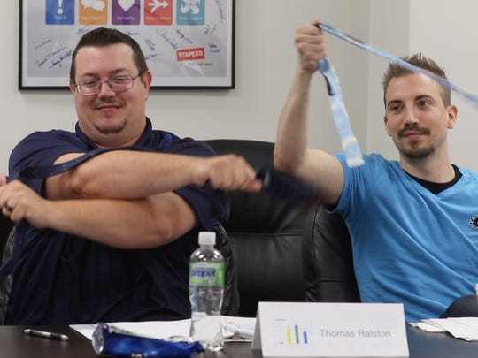 Thomas Ralston and Michael Trovato try and make a knot in one movement with a tie as part of an exercise in class.