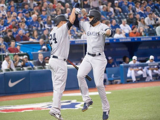 Mar 29, 2018; Toronto, Ontario, CAN; New York Yankees right fielder Giancarlo Stanton (27) celebrates a home run with catcher Gary Sanchez (24) in the ninth inning during the Toronto Blue Jays home opener at Rogers Centre. The New York Yankees won 6-1.