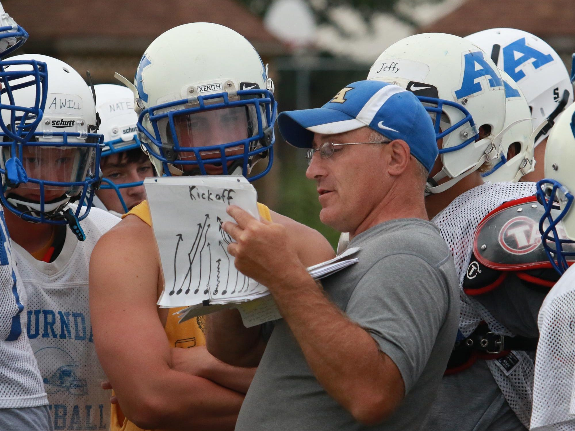 Players crowd around special teams coach John Karl as they work on kick-offs during practice at Auburndale, Aug. 7.