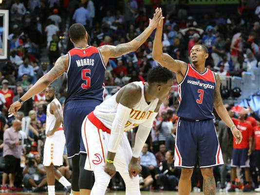 Washington Wizards' Markieff Morris (5) and Bradley Beal celebrate their victory over the Atlanta Hawks in Game 6 of a first-round NBA basketball playoff series on Friday, April 28, 2017, in Atlanta. (Curtis Compton/Atlanta Journal-Constitution via AP)