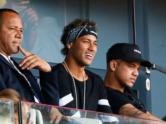 Brazilian soccer star Neymar smiles as he watches the match at the Parc des Princes stadium in Paris, Saturday, Aug. 5, 2017, after his official presentation to fans ahead of Paris Saint-Germain's season opening match against Amiens. Neymar would not play in the club's season opener as the French football league did not receive the player's international transfer certificate before Friday's night deadline. The Brazil star became the most expensive player in soccer history after completing his blockbuster transfer from Barcelona for 222 million euros ($262 million) on Thursday. (AP Photo/Francois Mori)