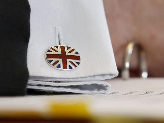 A cuff button of British Secretary of State for International Trade Liam Fox shows the Union Jack. British Prime Minister Theresa May sought a compromise Monday with opposition leader Jeremy Corbyn in hopes of securing his backing for a divorce deal with the European Union.