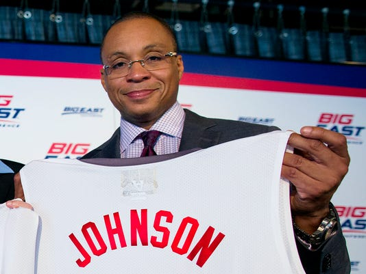 """FILE - In this Oct. 16, 2013, photo, basketball commentator Gus Johnson holds a jersey during a news conference during the Big East NCAA college basketball media dayin New York. Fox has picked Johnson as its lead soccer announcer and is teaming him with former U.S. star Eric Wynalda. """"I completely realize that Gus and Eric, having two American voices, is a change for the hard core, absolutely,"""" says Fox Sports President Eric Shanks. """"It's a change that I believe in."""" (AP Photo/Craig Ruttle, File)"""