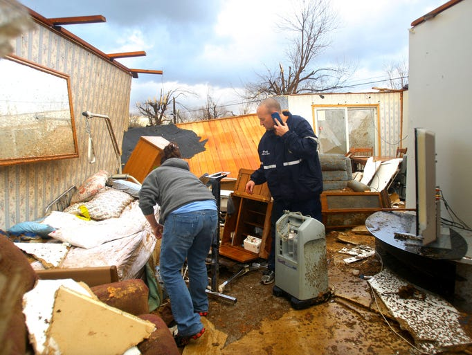 Stacy Broniak and Todd Woolf, a Grissom firefighter, sift through debris looking for medication and oxygen supplies for Broniak's grandmother, Colleen Carney, who lived in the destroyed house  in Kokomo, Ind.