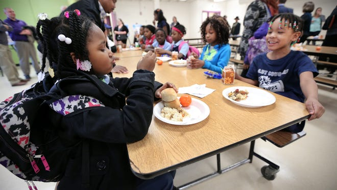 Seven-year-old Lilly Dariri, left, and 6-year-old Essence Davis enjoy a free meal after the celebration ceremony and ribbon cutting that unveiled the newly renovated and expanded kitchen at the Boys & Girls Club on E. 30th Street in Indianapolis on Thursday.