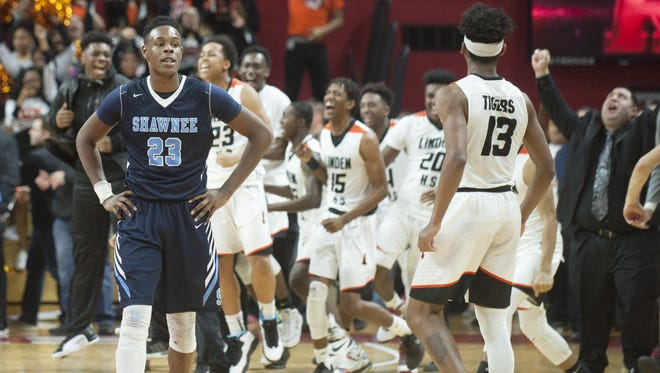 Shawnee's Daevon Robinson walks off the court as members of the Linden High School boys basketball team celebrate after Linden defeated Shawnee 57-41 in the boys basketball Group 4 state final played at the Louis Brown Athletic Center at Rutgers University on Sunday.