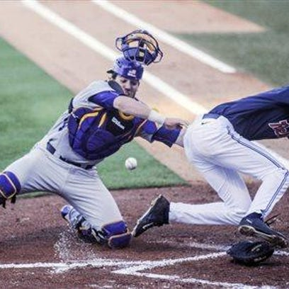 Ole Miss infielder Ryan Olenek (2) scores as the ball gets away from LSU catcher Jordan Romero (28) during the first inning of Thursday's game.
