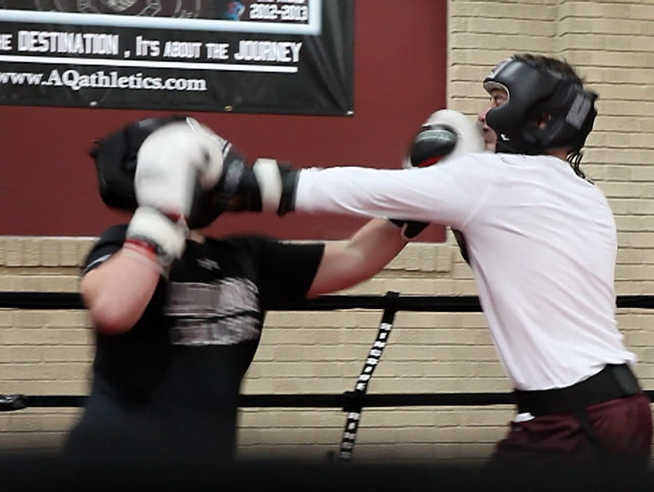 Michael Bohme and Mike Robertson spar at boxing practice.