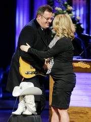 Vince Gill and Carrie Underwood hug after performing a duet during the funeral service for Little Jimmy Dickens on Thursday in the Grand Ole Opry House in Nashville. In front of them are boots and a hat belonging to Dickens, who died Jan. 2 at age 94.