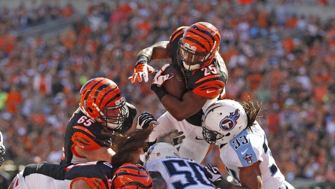 Cincinnati Bengals running back Giovani Bernard (25) goes over the top to score a touchdown against the Tennessee Titans during the third quarter of their game against the Tennessee Titans at Paul Brown Stadium in downtown Cincinnati Sunday September 21, 2014.