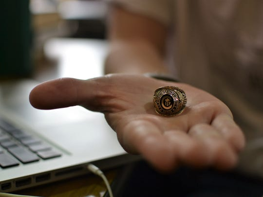 Stephen Linnell, a senior computer science major at Clemson University, holds out his class ring. His parents spent around $900 on it as a graduation gift, he said.