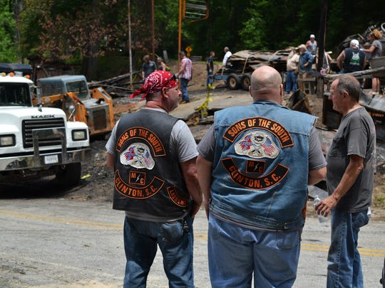 Jimmy Swaney, at left, Richard Thackston, center, and Kerwad Gantt watch as volunteers clear scrap metal and charred debris from where Bob's Place used to stand. The bar, which sat at 1490 Moorefield Memorial Hwy, burned down on May 20.