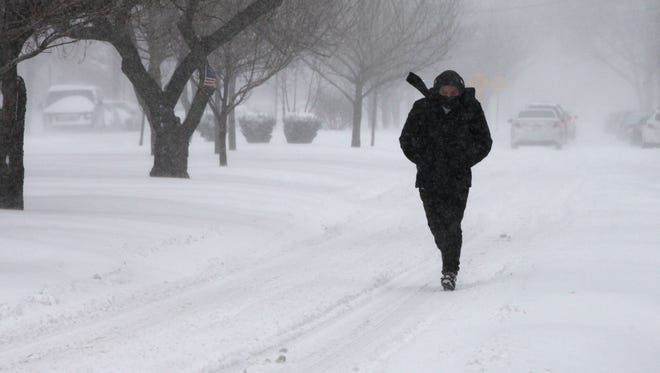 Yonkers resident makes his way through the snow by walking in the street along Rumsey Road.