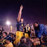 Clawson natives Jon Jansen (left) and Mark Campbell lift the Little Brown Jug trophy after the University of Michigan's 1997 victory over Minnesota.