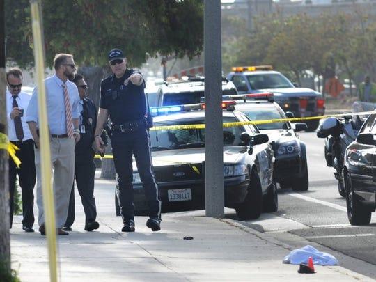Investigators work at the scene of a homicide on June
