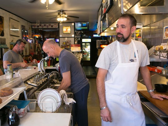 Damian Muzzi chats with his customers during breakfast at Angelo's Luncheonette, which is celebrating its 50th birthday with a big party on Saturday for its customers.