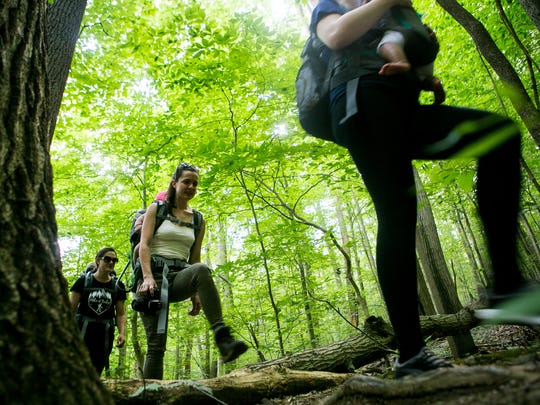 Hannah Starke of Lincoln University, Pa. carries her daughter Hazel as the group Hike It Baby Delaware enjoys a 3-mile hike in the Middle Run area of Pike Creek.