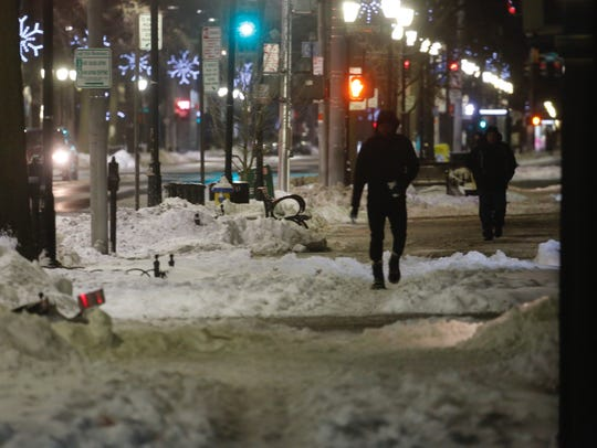 People negotiate patches of snow in White Plains, Friday,