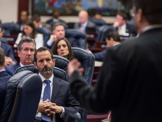 Florida Rep. Michael Bileca, R-Miami, center left, listens as Rep. Chris Latvala, R-Clearwater, speaks on the school safety bill in the House chamber at the Florida Capital in Tallahassee on March 7.