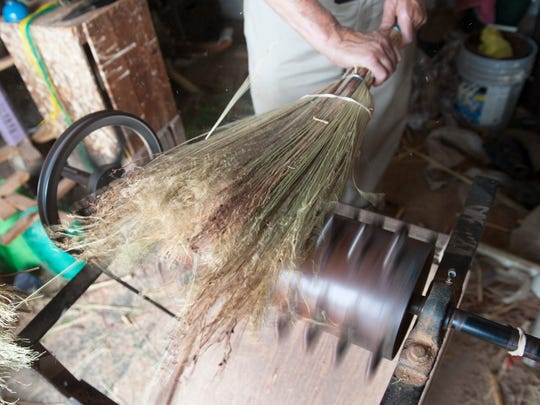 Sam Moyer works on making a broom in a workspace that