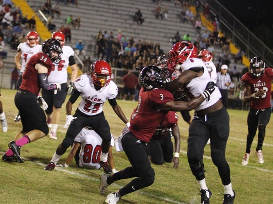 Leon's Sam Thomas fends off approaching Chiles defenders.