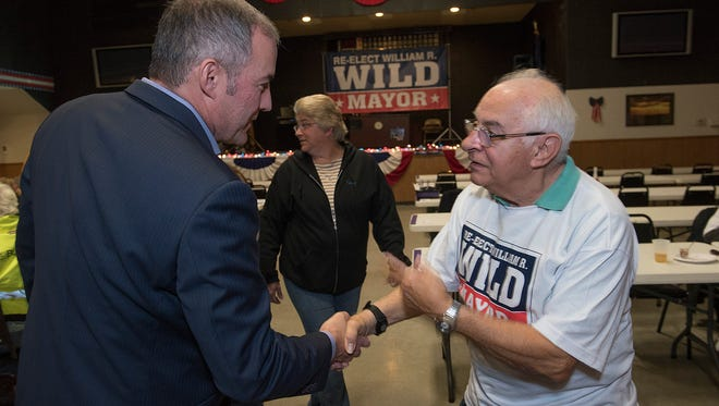 Mayor William Wild speaks with supporter Regis Miller. Passing in the background is Tina Moutoux.