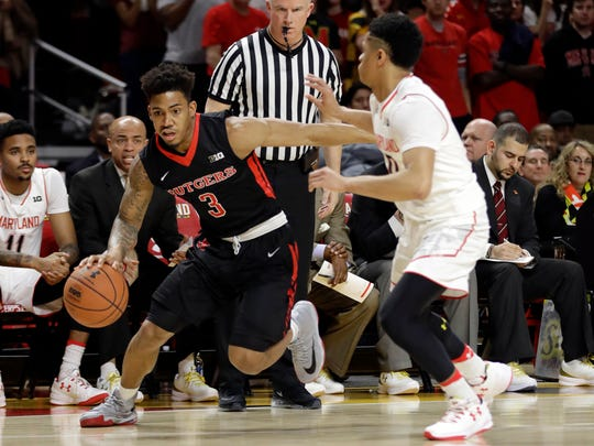 Rutgers guard Corey Sanders, left, drives around Maryland guard Anthony Cowan.