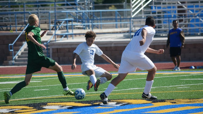Bloomfield's Terrance Phillips, center, slides down trying to get the deflection at center-pitch against Los Alamos' Andreas Runde, left, during the second half of Saturday's match at BHS.