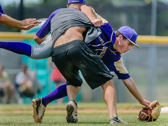 Fowlerville pitcher Eric Fritz ,right, is tackled by